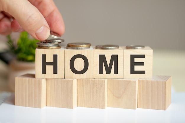 나무 조각에 쓰여진 단어 집. 남자의 손은 큐브의 표면에 동전을 놓습니다.