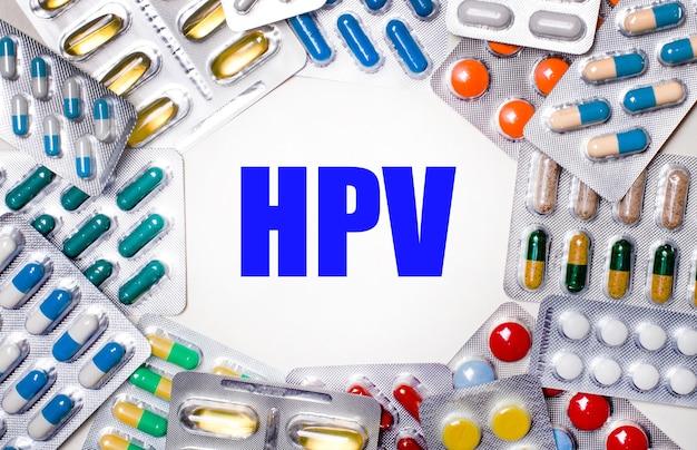 Hpv라는 단어는 알약이 든 다양한 색상의 패키지로 둘러싸인 밝은 배경에 쓰여 있습니다. 의료 개념