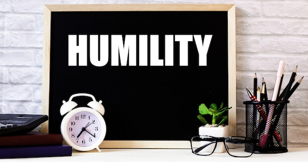 칠판에 흰색 알람 시계, 안경, 화분, 스탠드에있는 연필 옆에 humility라는 단어가 적혀 있습니다.