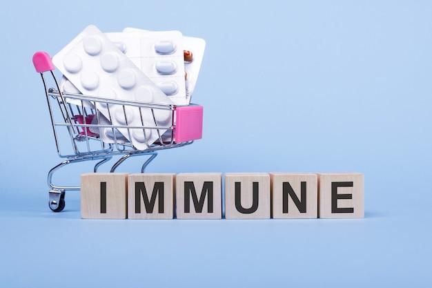 Слово immune на деревянных кубиках, на синем фоне с таблетками в тележке для покупок.