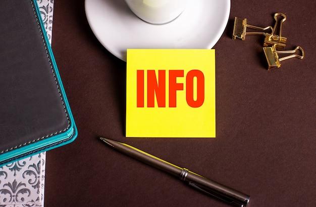 コーヒーカップと日記の近くの茶色の背景に黄色い紙に書かれたinfoという単語