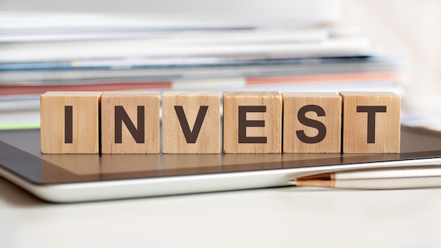 Investという言葉は、タブレットの上に立っている木製の立方体に書かれ、背景にはドキュメントのスタック、選択的な焦点があります。ビジネス、教育、金融、マーケティングの概念に使用できます。