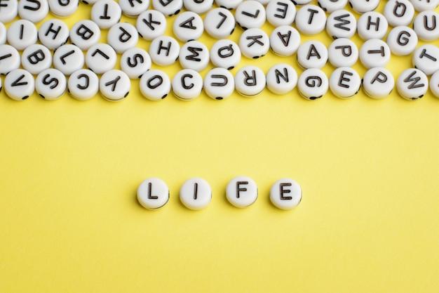 白いプラスチックブロックで作られたlifeという言葉は、上部に多くの文字があります