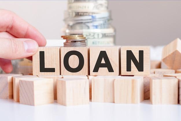 나무 블록과 돈, 비즈니스 개념으로 은행에 단어 대출