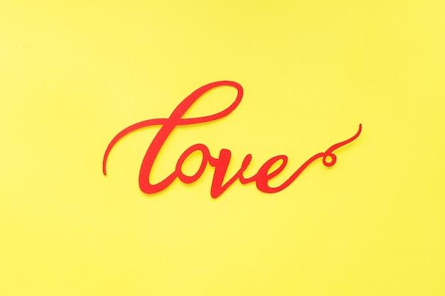 Слово любовь и красные сердца на желтом фоне, вид сверху. праздничная открытка на день святого валентина. плоская планировка.