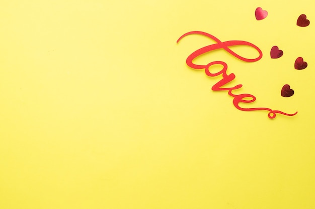 노란색 배경, 평면도에 단어 사랑과 붉은 마음. 발렌타인 데이 크리스마스 카드. 평평하다.