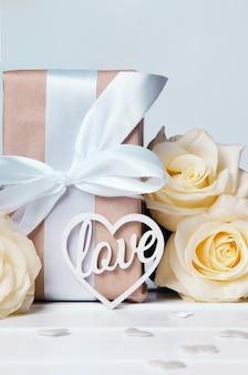 Слово любовь белыми буквами на подарочных коробках с белыми лентами и желтыми розами