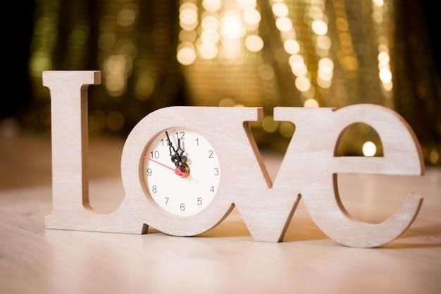 愛という言葉は、黄金色の面を持つ時計の形をしています。木製時計