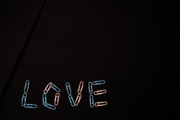 사랑이라는 단어는 검정색 배경에 종이 클립에서 배치됩니다. 종이 클립은 분홍색과 파란색입니다. 발렌타인 데이의 개념.