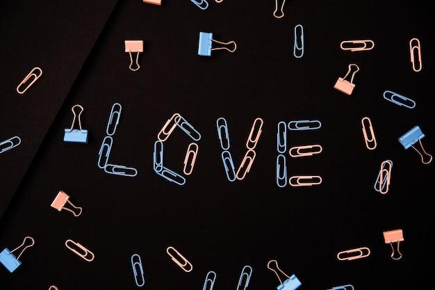 Слово любовь выложено из скрепок на черном фоне. скрепки розовые и синие. концепция дня святого валентина.