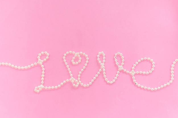사랑이라는 단어는 분홍색 질감의 배경에 구슬로 되어 있습니다. 발렌타인 데이