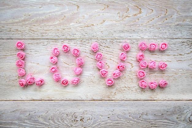 Слово love выполнено из маленьких искусственных розовых роз на светлом деревянном деревенском фоне, вид сверху.