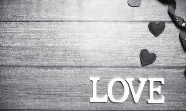 나무 배경에 흰색 나무 글자로 구성된 사랑이라는 단어