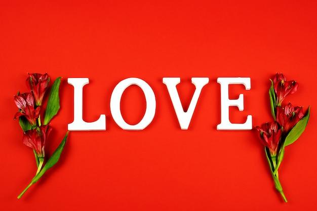 Alstroemeria 꽃과 붉은 벽에 단어 사랑. 발렌타인 데이