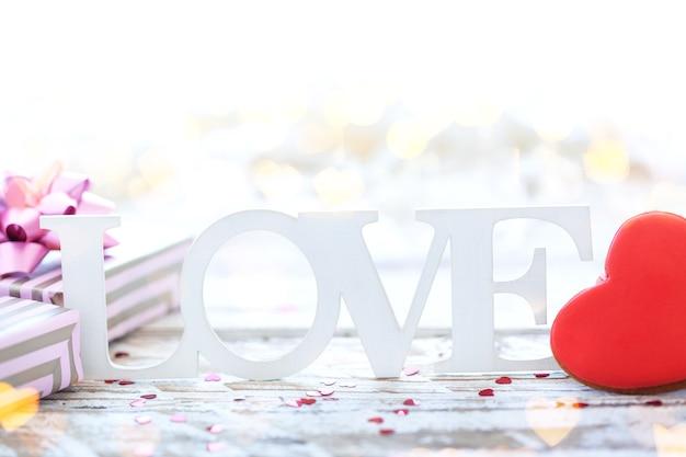 木製のテーブルにクッキーのハートとギフトボックスと愛という言葉。バレンタインデーのコンセプト。セレクティブフォーカス。