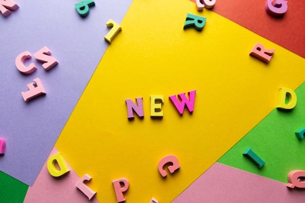 木製の色とりどりの文字で作られた単語色付きの背景に散らばった文字