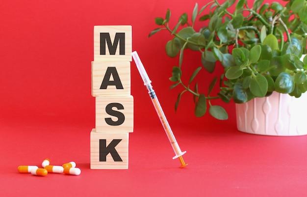 마스크라는 단어는 의료용 약물로 빨간색 표면에 나무 큐브로 만들어져 있습니다.
