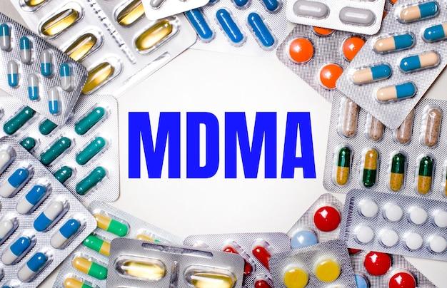 Mdma라는 단어는 알약이 든 여러 색상의 패키지로 둘러싸인 밝은 배경에 작성됩니다. 의료 개념