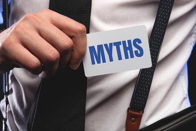 Слово мифы молодой человек, держащий заглушку на белом фоне с виньеткой.