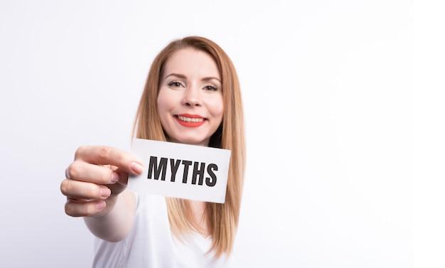 Слово мифы молодая женщина, держащая заглушку на белом фоне с виньеткой.