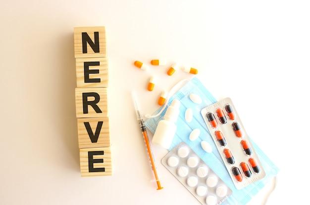 神経という言葉は、白い背景に医薬品と医療用マスクが付いた木製の立方体でできています。