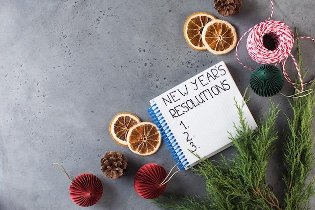 Слово новогоднее разрешение написано в белой записной книжке на сером новогоднем фоне копией пространства