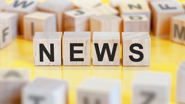 ニュースという言葉は、木製の立方体の構造に書かれています。明るい黄色の背景のブロック。財務コンセプト。セレクティブフォーカス