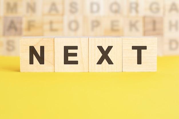 次の言葉は、明るい黄色の表面の木製の立方体に書かれています。背景には、異なる文字の立方体の行があります。ビジネスと金融の概念