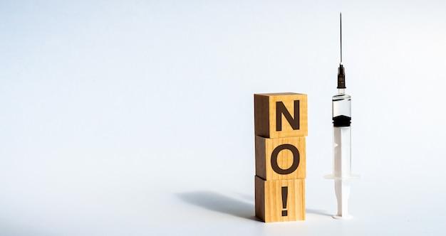 '아니오'라는 단어는 투명한 의료용 주사기 옆 테이블에 누워있는 나무 조각에 적혀 있습니다. 흰 배경. 개념.
