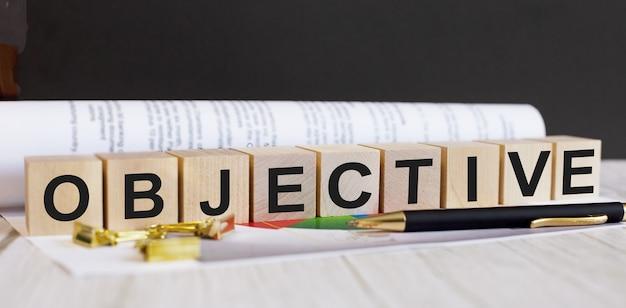 Слово объектива написано на деревянных кубиках рядом с ручкой и документом.