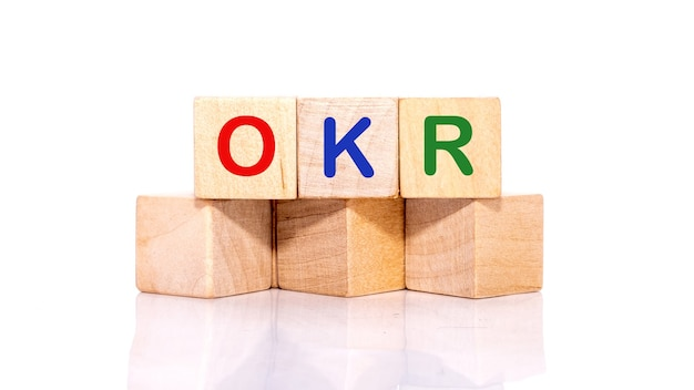 Okr이라는 단어는 흰색 표면에 고립 된 나무 블록에 기록됩니다.