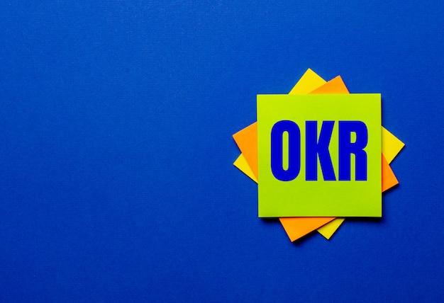 Слово okr objective key results написано на ярких стикерах на синем фоне.