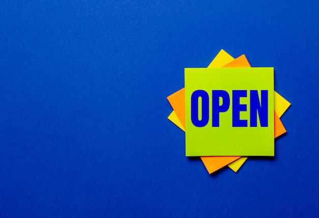 Openという言葉は青い背景の明るいステッカーに書かれています