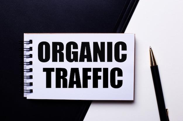 Слово organic traffic написано красным на черно-белом фоне рядом с ручкой.