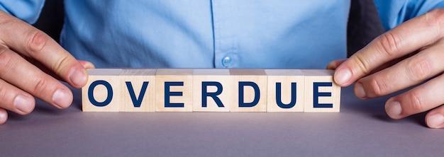 Слово overdue составлено мужчиной из деревянных кубиков.
