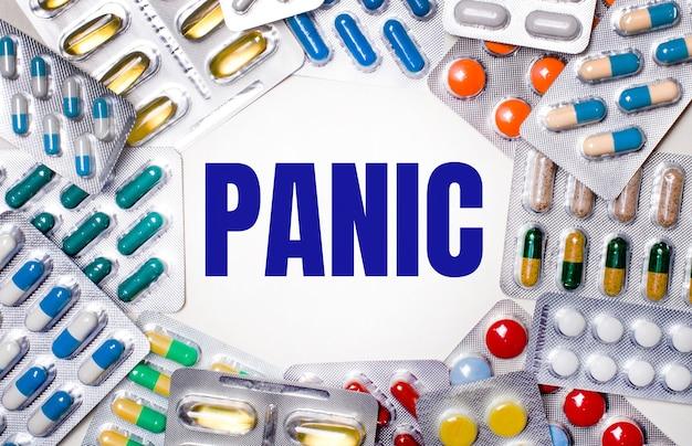 Слово паника написано на светлом фоне в окружении разноцветных упаковок с таблетками. медицинская концепция