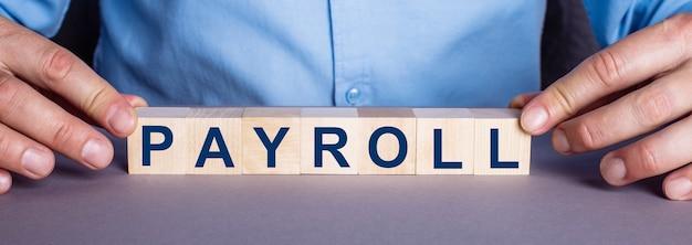 Слово payroll составлено из деревянных кубиков человеком.