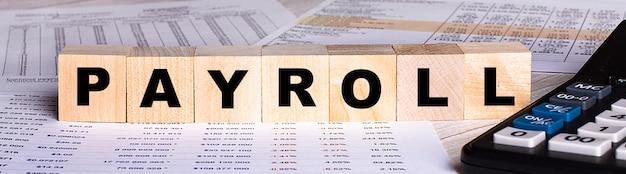 Слово payroll написано на деревянных кубиках рядом с графиками и калькулятором.