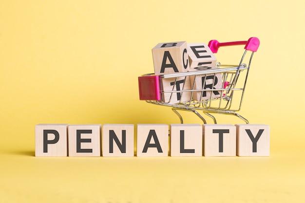 ショッピングカートと黄色の背景に、木製の立方体にペナルティという言葉。