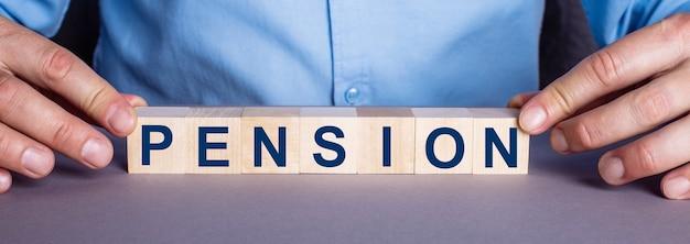 Слово пенсия составлено мужчиной из деревянных кубиков. бизнес-концепция.