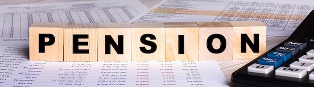 Слово пенсия написано на деревянных кубиках возле графиков и калькулятора.