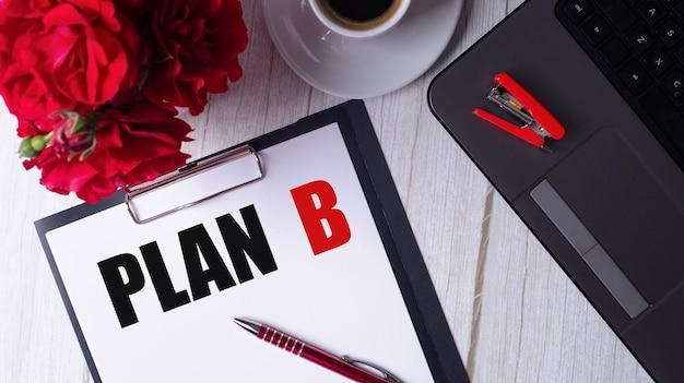 Слово план б написано красным на белом блокноте рядом с ноутбуком, кофе, красными розами и ручкой.