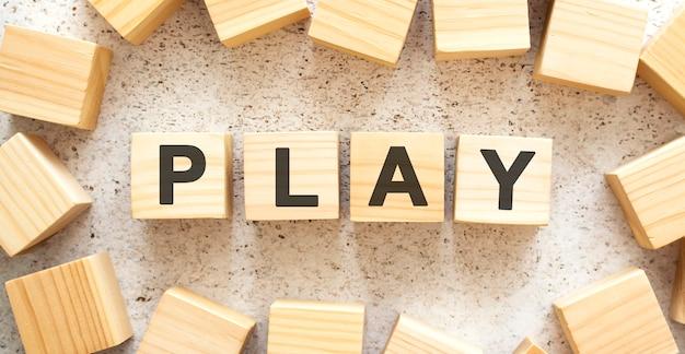 Слово play состоит из деревянных кубиков с буквами, вид сверху на светлой поверхности.