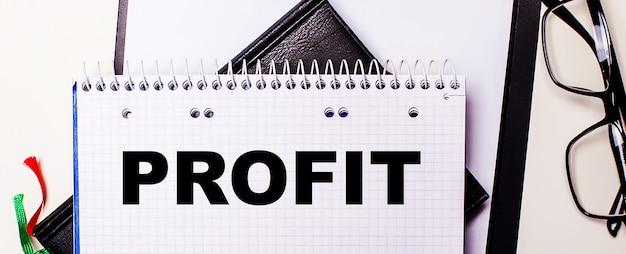 Profitという言葉は、黒いフレームのメガネの横にある白いノートに赤で書かれています。