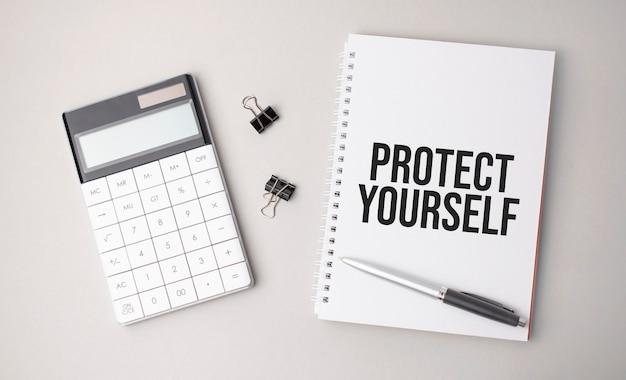 흰색 배경에 펜, 계산기, 보고서 옆에 protect yourself라는 단어가 쓰여 있습니다. 비즈니스 개념