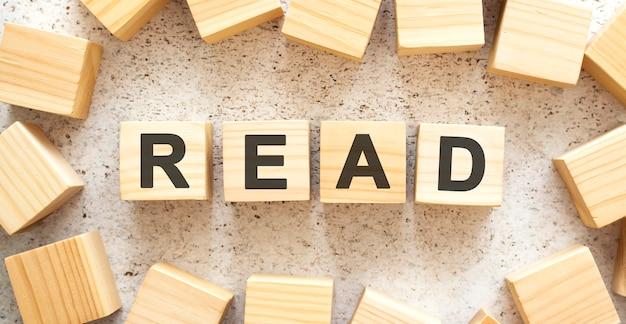 Слово read состоит из деревянных кубиков с буквами, вид сверху на светлой поверхности.