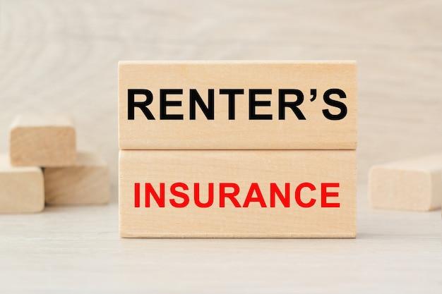На деревянной конструкции из кубиков написано слово арендаторская страховка.