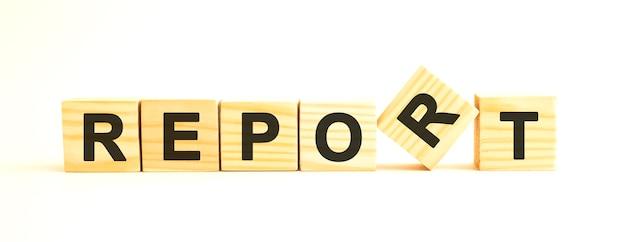 보고서라는 단어. 흰색 표면에 고립 된 문자로 나무 큐브