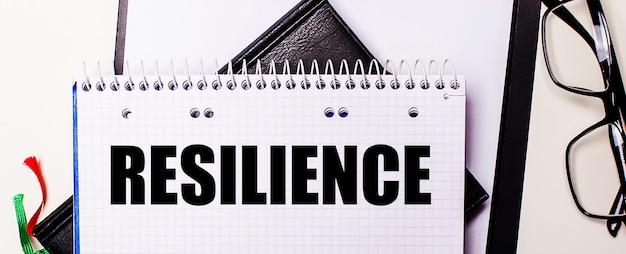 Resilience라는 단어는 검은 색 안경테 옆의 흰색 노트북에 빨간색으로 적혀 있습니다.