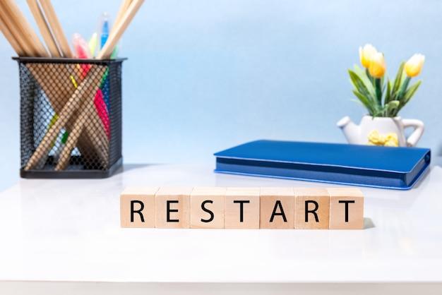 再起動という言葉は、オフィスのデスクトップ上の木製のブロックに書かれています。
